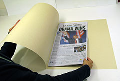image of conservators placing newspaper in acid-free paper folder