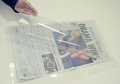 image of conservator placing newspaper in transparent polyester folder
