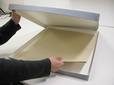 image of conservator placing newspaper in a flat storage box